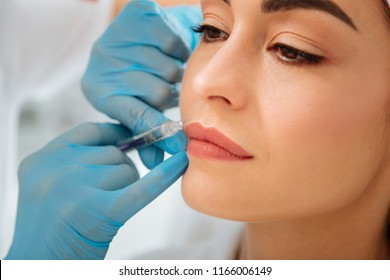 For beauty. Nice good looking woman looking at the syringe while having an injection in her face