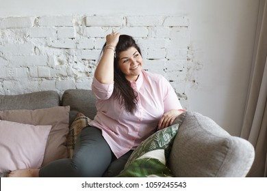 Beauty, obesity and body positive movement concept. Indoor shot of gorgeous attractive young overweight Caucasian brunette woman with big breast and hips enjoying good sunny day, resting on couch