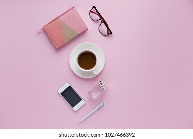 Beauty office desk with cup of cofee, notebook, pen and mobile phone on pink background. Top view. Flat lay lifestyle concept.