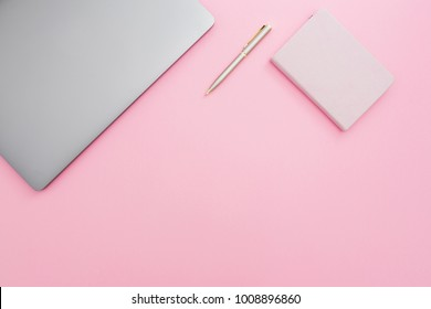 Beauty office desk with laptop, notebook and pen on pastel pink background. Top view. Flat lay lifestyle concept.