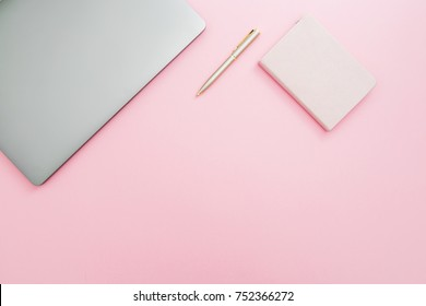 Beauty office desk with laptop, notebook and pen on pink background. Top view. Flat lay lifestyle concept.
