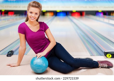 Beauty on the bowling alley.Beautiful young women sitting on the floor against bowling alleys