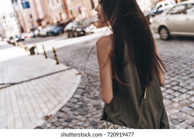 Beauty on the go. Rear view of attractive young woman looking away while walking down the street outdoors