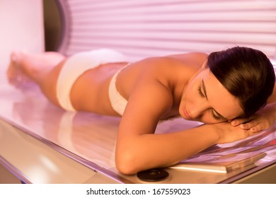 Beauty on tanning bed. Top view of attractive young woman tanning in solarium