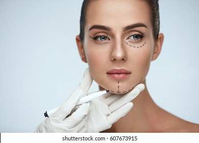 Beauty Operation. Closeup Of Beautician Hand Drawing Surgical Lines On Beautiful Young Woman Face. Portrait Of Sexy Woman With Soft Skin Before Plastic Surgery. Facial Treatment. High Resolution