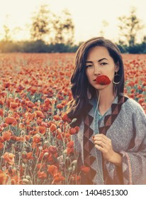Beauty outdoor portrait of brunette young woman with red poppy near her face in flower meadow, looking at camera.