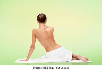beauty, people and bodycare concept - beautiful young woman in white towel with bare top over green natural background