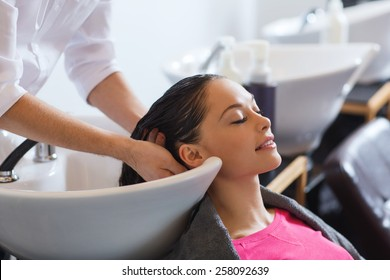 beauty and people concept - happy young woman with hairdresser washing head at hair salon