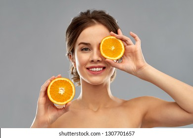 beauty and people concept - smiling young woman with oranges over grey background