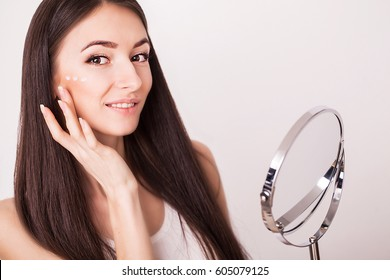 beauty, people, cosmetics, skincare and health concept - happy smiling young woman applying cream to her face.