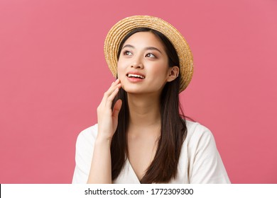 Beauty, people emotions and summer leisure and vacation concept. Dreamy tender, romantic asian woman in straw hat and white dress, looking upper left corner and gently touch face