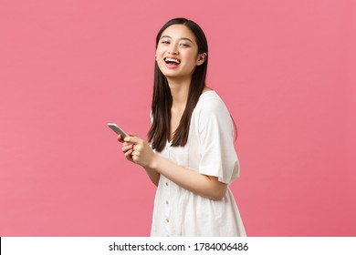 Beauty, people emotions and technology concept. Beauiful asian girl over romantic pink background laughing as using mobile phone. Female model messaging, checking-out new application