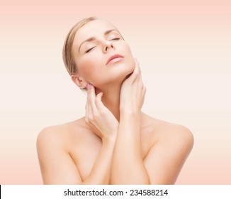 beauty, people and health concept - beautiful young woman with closed eyes touching her neck over pink background