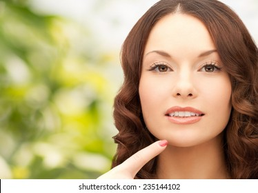 beauty, people and health concept - beautiful young woman pointing finger to her chin over green background