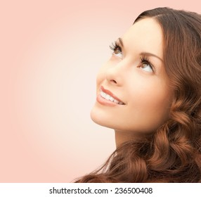beauty, people and health concept - beautiful young woman looking up over pink background