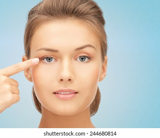 beauty, people and health concept - beautiful young woman pointing finger to her eye over blue background