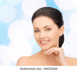 beauty, people and health concept - beautiful young woman touching her face over blue lights background