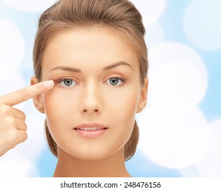 beauty, people and health concept - beautiful young woman pointing finger to her eye over blue lights background