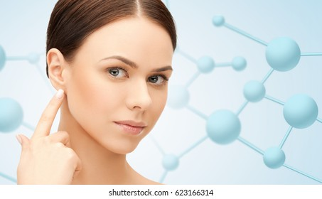 beauty, people and health concept - beautiful young woman face over blue background with molecules