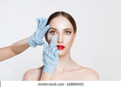 Beauty, people and health concept. beautiful young woman getting ready for eyelid lift, blepharoplasty plastic surgery doctors's hands in blue gloves pointing fingers to her eye over white background.
