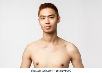 Beauty, people and home concept. Close-up portrait of handsome young asian man with naked torso, looking camera confident and pleased, standing white background, go to shower