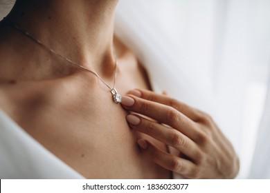 beauty, people and jewelry concept - beautiful young woman wearing shiny diamond pendant