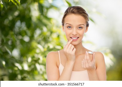 beauty, people and lip care concept - smiling young woman applying lip balm to her lips over green natural background