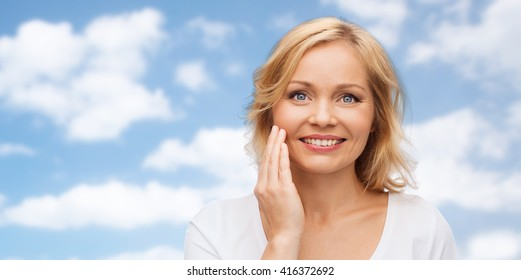 beauty, people and skincare concept - smiling woman in white shirt touching face over blue sky and clouds background