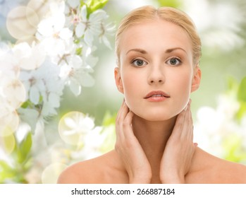 beauty, people, summer, spring and health concept - beautiful young woman touching her neck over green blooming garden background