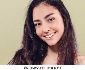 Beauty People Woman face Portrait. Beautiful Spa model Girl with Perfect Fresh Clean Skin. Brunette female looking at camera and smiling. Youth and Skin Care Concept.