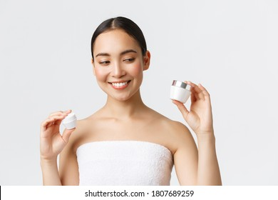 Beauty, personal care, spa salon and skincare concept. Close-up of beautiful asian female in bath towel holding two creams, eye and face nourishing products, smiling, skin treatment