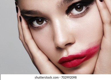 Beauty photography of fashion model with blurred drama makeup holding her face.