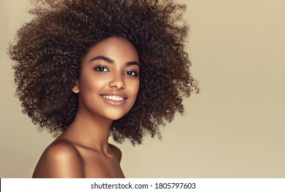 Beauty portrait of african american black  woman with clean healthy skin on beige background. Life style and cosmetic. Smiling beautiful afro girl.Curly  hair