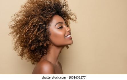 Schönes Porträt von afrikanischem amerikanischem Mädchen mit sauberer, gesunder Haut auf beigem Hintergrund. Lächelnd traumhaft schöne schwarze Frau.Curly Haar im Stil von afro