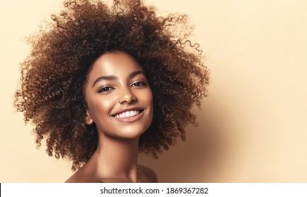 Beauty portrait of african american girl with clean healthy skin on beige background. Smiling dreamy beautiful black woman.Curly hair in afro style - Shutterstock ID 1869367282
