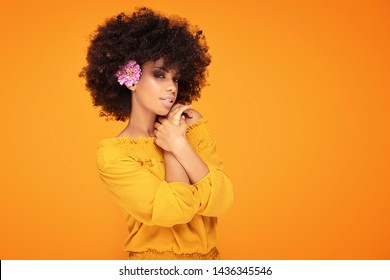 Beauty portrait of african american woman with glamour makeup, afro hair and fresh flowers posing on yellow studio background.