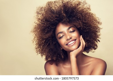 Beauty portrait of african american woman with clean healthy skin on beige background. Smiling beautiful afro girl.Curly black hair - Shutterstock ID 1805797573