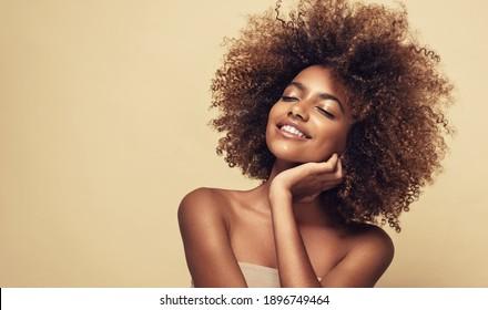 Schönes Porträt afrikanischer Amerikanerin mit sauberer, gesunder Haut auf beigem Hintergrund. Lächeln schön nach Mädchen.Curly schwarze Haare