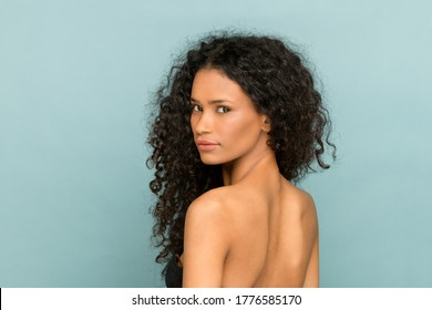 Beauty portrait of a Afro American woman with gorgeous long curly hair turning to look back over her shoulder at the camera against a blue studio background