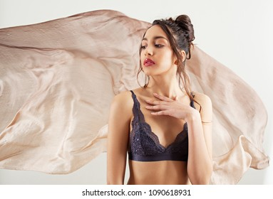 Beauty portrait of asian exotic young woman in lingerie bra against silk floating fabric background, healthy skin care, cosmetics make up. Female with flawless skin, ethereal and dreamy, lifestyle.