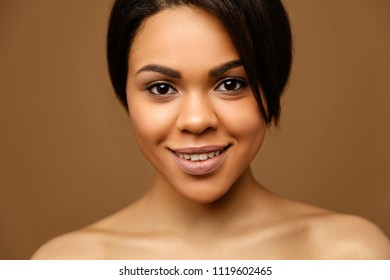 Beauty Portrait of attractive African American young woman with perfect skin and natural make up. Beautiful brunette model. Skin Face Care Concept. Looking on camera against brown background