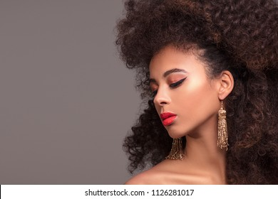 Beauty portrait of attractive african american woman with long afro hairstyle and glamour makeup, studio shot.