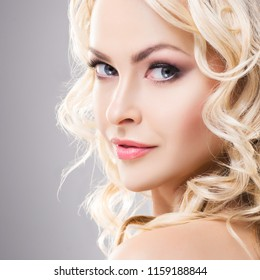 Beauty portrait of attractive blond woman with curly hair and a beautiful hairstyle. Makeup and cosmetics concept.