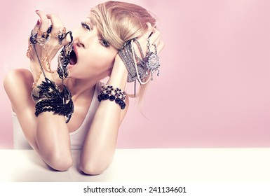 Beauty portrait of attractive delicate blonde woman with jewelry on hands. Girl looking at camera. Pink background.