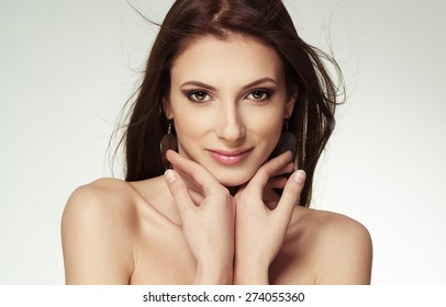 Beauty portrait of attractive female touching her face. Skin care, cosmetics and makeup concept.