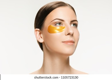 Beauty portrait of an attractive girl with a gold patch under the eyes. Spa treatment and face beauty concept. Female face care and perfect skin concepts