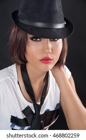 A beauty portrait of an attractive girl wearing a hat and tie on black background, fashion