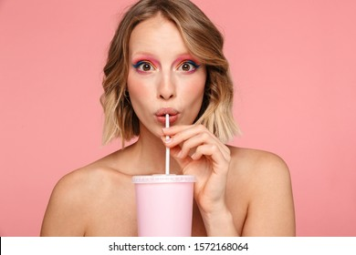 Beauty portrait of an attractive lovely young topless blonde haired woman standing isolated over pink background, drinking from a plastic cup with straw