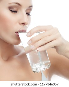 beauty portrait of attractive young  caucasian woman isolated on white studio shot drinking pure fresh water beautiful perfect face skin closeup glass of water