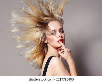 beauty portrait of attractive young caucasian woman blond on beije background studio shot hair wind blowing red lips looking at camera hand nails
